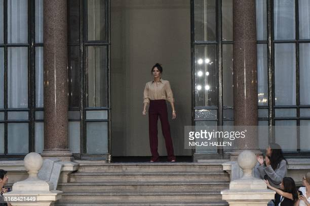 British designer Victoria Beckham acknowledges the crowd after showcasing her collection during a catwalk show at the Foreign and Commonwealth office...