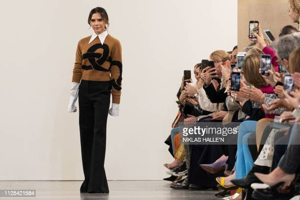 British designer Victoria Beckham acknowledges the crowd during her 2019 Autumn / Winter collection catwalk show at London Fashion Week in London on...