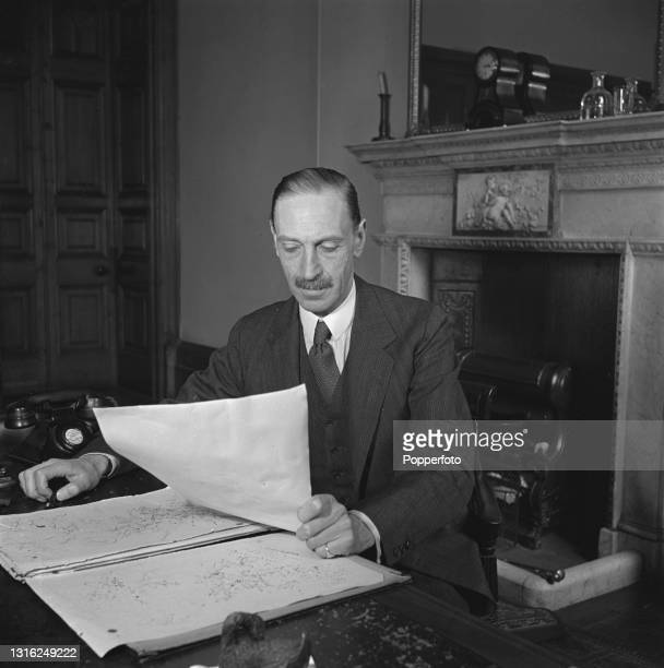 British diplomat and civil servant Sir Orme Sargent , deputy under-secretary, checks documents at his desk at the Foreign and Commonwealth Office in...