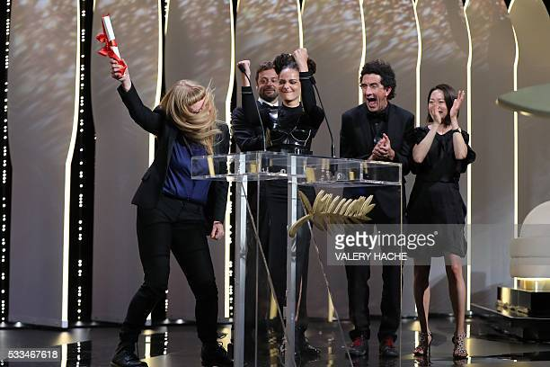 TOPSHOT British director Andrea Arnold celebrates on stage with US actress Sasha Lane and cinematographer Robbie Ryan after being awarded with the...