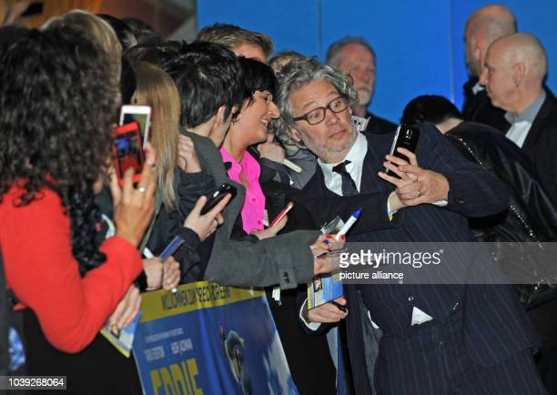British director Dexter Fletcher takes selfies with fans as he arrived for a special screening of 'Eddie The Eagle' in Munich Germany 20 March 2016...