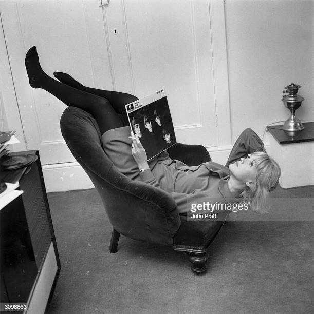 British disc jockey and television presenter Annie Nightingale relaxing at her home in Brighton with a copy of the Beatles album 'With The Beatles'...