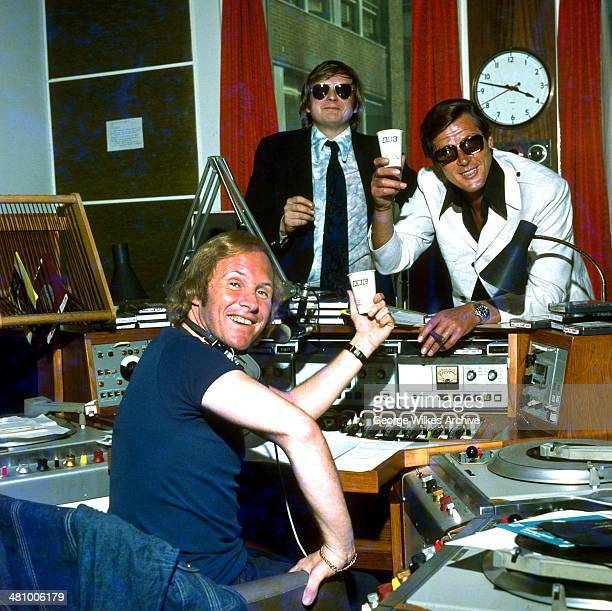 British disc jockey David Hamilton poses in his studio with television and film actor Roger Moore and an unidentified man, London, England, 1975.