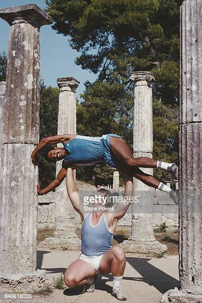 British discus thrower Richard Slaney holds aloft decathlete Daley Thompson on 1 March 1984 at the ancient Greek Temple of Hera in Olympia Greece