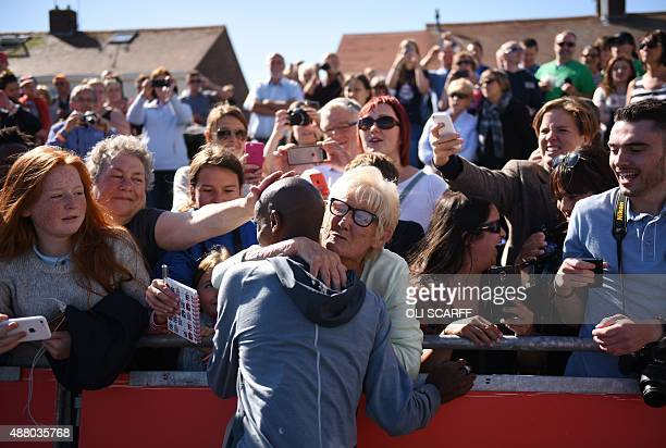 British distance runner Mo Farah celebrates with a fan after winning men's elite race in the Great North Run half-marathon in South Shields, north...