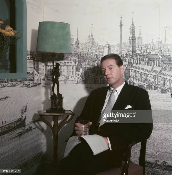 British dramatist and playwright Terence Rattigan posed holding a glass and a play script in a living room in 1952. The wall behind is decorated with...