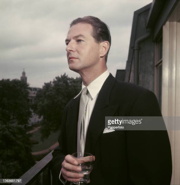 British dramatist and playwright Terence Rattigan posed holding a glass on a balcony in 1952.