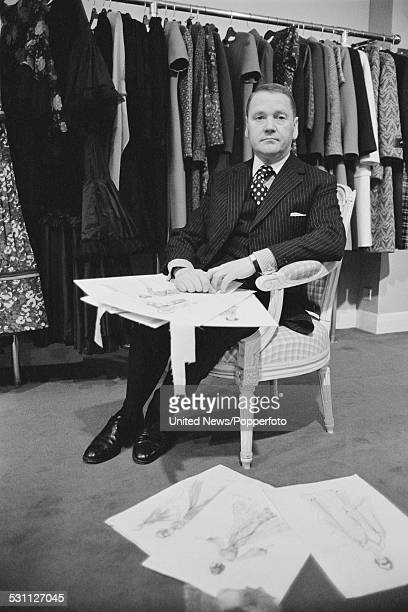 British dress designer for Queen Elizabeth II Ian Thomas pictured sitting with dress designs in London on 9th December 1976
