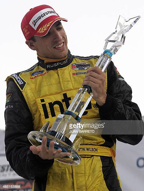 British driver Justin Wilson from RuSPORT team celebrates holding the trophy after winning the Champ Car GP at the Autodromo Hermanos Rodriguez in...