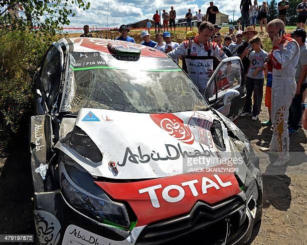 British driver Kris Meeke and his Irish codriver Paul Nagle react next to their destroyed Citroen DS3 WRC on July 2 2015 in Mikolajki north Poland...