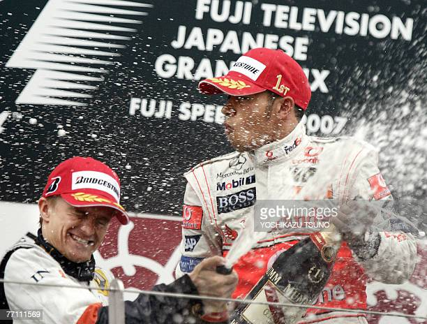 British driver Lewis Hamilton of McLaren Mercedes and Finnish driver Heikki Kovalainen of Renault spray champagne on the podium after coming in first...