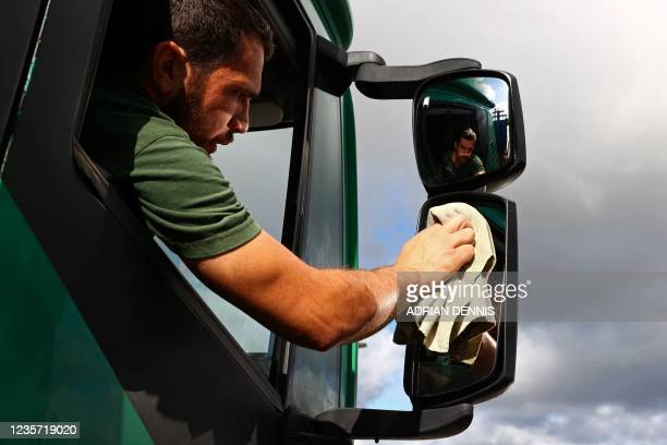 British driver Steven Abbott sits in his cab while taking a break from driving at Ashford International truck stop, in south-east England on October...