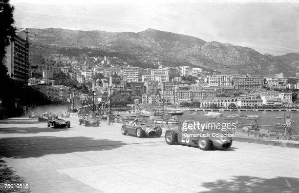 British driver Stirling Moss, the eventual race winner, has his Maserati 250F in front of Eugenio Castellotti's Ferrari-Lancia as the field slows for...