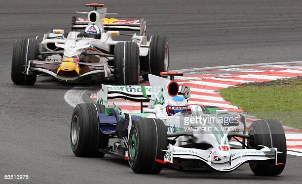 British drivers Jenson Button on HondaRacing team and David Coulthard of Red Bull Racing take a bend during the second free practice at the...