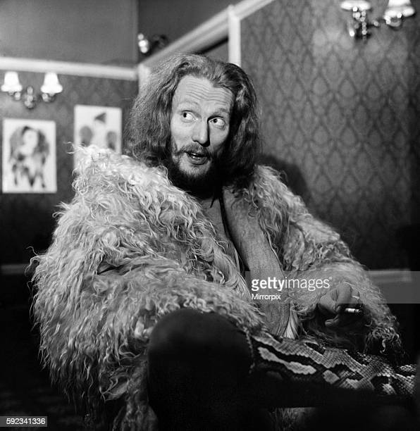 British drummer Ginger Baker former member of the pop group Cream in curly shearling sheep wool coat and snakeskin high boots sitting on a chair...