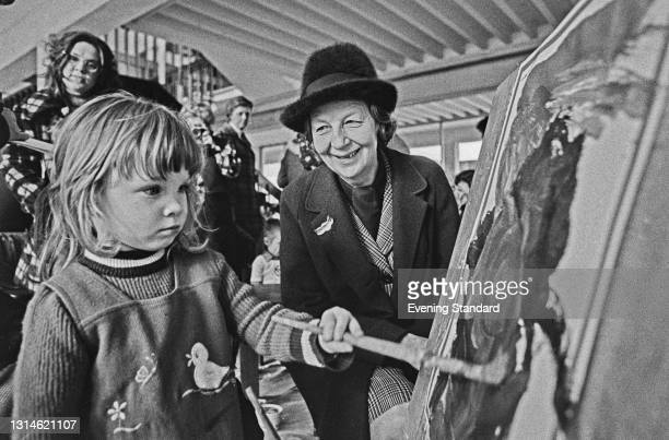 British educational reformer Bridget, Lady Plowden watches a child work on a painting, UK, 19th March 1974. Lady Plowden is vice-chair of the BBC.