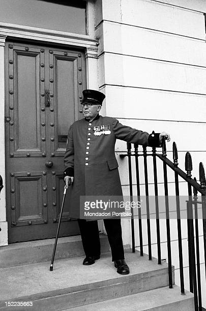 A British elderly man with medals pinned on his chest standing outside the door of his house London 1960s