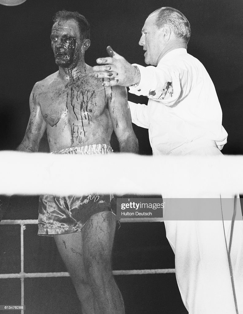 British Empire Heavyweight Champion Henry Cooper, with blood streaming from his left eye, is told by referee Tommy Little, that the fight is over. The referee decided to stop the fight in the fifth round of the contest at Wembley against Cassius Clay, when Cooper's eye got too bad.