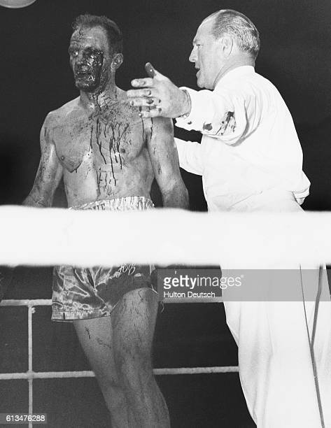 British Empire Heavyweight Champion Henry Cooper with blood streaming from his left eye is told by referee Tommy Little that the fight is over The...