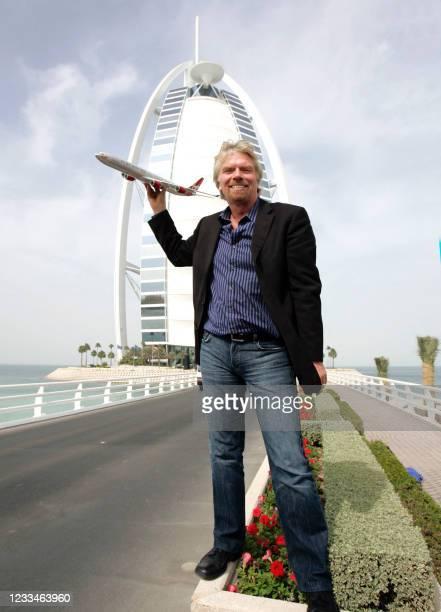 British entrepreneur Sir Richard Branson, who owns Virgin Group, holds a model Virgin airplane in front of Dubai's landmark Burj Al-Arab hotel 17...