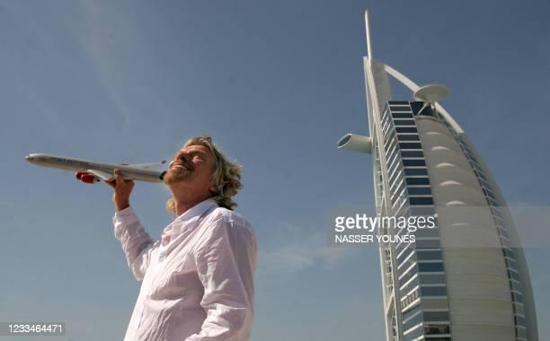 British entrepreneur Sir Richard Branson, who owns Virgin Group, holds a model Virgin airplane in front of Dubai's landmark Burj Al-Arab hotel 28...