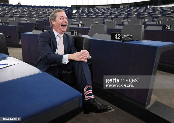 TOPSHOT British eurodeputy Nigel Farage shows off his Union Jack socks as he arrives for a plenary session at the European Parliament on October 2...