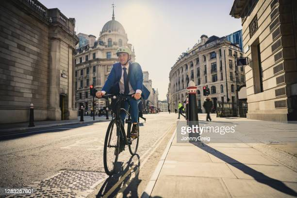 british executive enjoying sunny ride to work by bicycle - cycling stock pictures, royalty-free photos & images