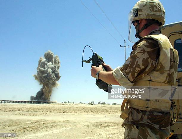 A British explosives expert sets off with a remote control detonator ammunitions found at a military base that belong to the Iraqi army in the...