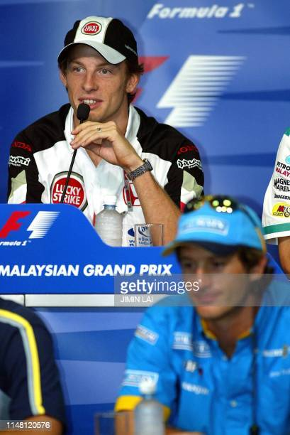 British F1 driver Jenson Button of BAR speaks to journalists during a press conference at the Sepang F1 Circuit while Italian Jarno Trulli of Renault...