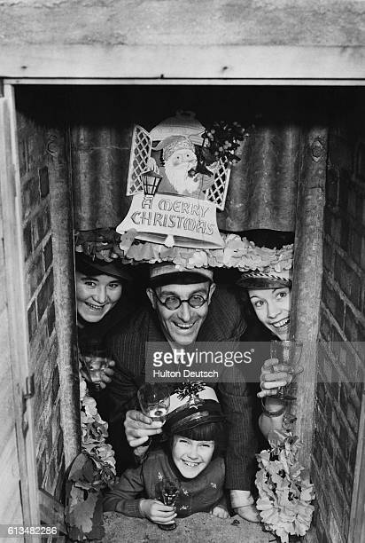 A British family enjoy Christmas in their Anderson air raid shelter December 23rd 1940