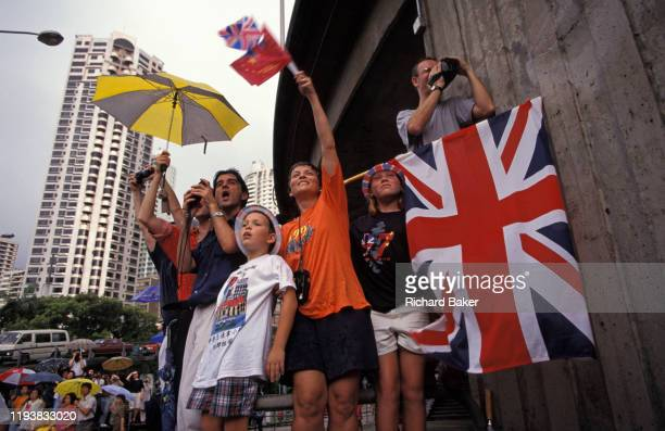 British family hoping to catch a glimpse of passing VIPs, wave Union Jack flags on the eve of the handover of sovereignty from Britain to China, on...