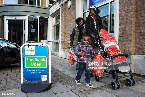 A British family leave the Trussell Trust Kingston foodbank having collected their emergency food supply from the charity The woman uses her son's...