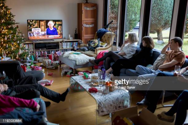 British family watch the Queen's speech to the nation on Christmas Day, a tradition started in 1932 and which she first broadcast on television in...