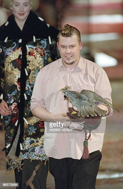 British fashion designer Alexander McQueen carries a falcon as he acknowledges at the end of the Givenchy 1997/98 Fall/Winter high fashion collection...