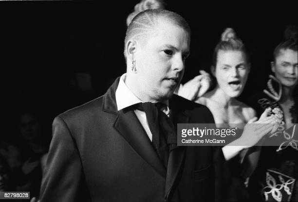British fashion designer Alexander McQueen with unidentified models in the background at a show of his fashions in March 1996 in New York City New...