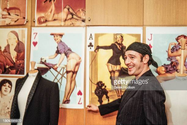 British fashion designer John Galliano poses with a series of giant playing cards adorned with pictures of models in sexy underwear affixed to a wall...
