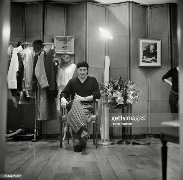 British fashion designer John Galliano wearing baggy striped trousers, a black bandana head covering and a V-neck sweater is pictured seated smoking...
