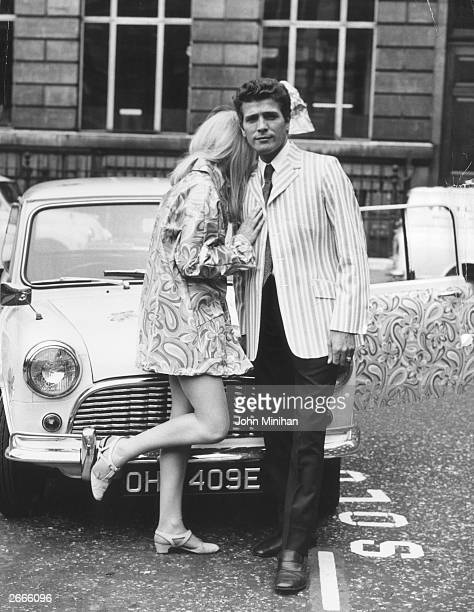 British fashion designer John Stephen standing in front of a decorated mini with Diana Harris