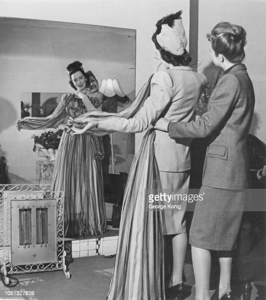 British fashion designer Joy Ricardo holds up an evening gown specially designed for Scottish actress Deborah Kerr London 7th October 1946