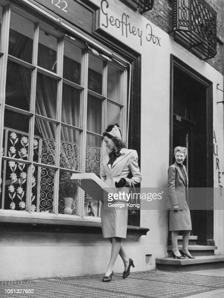 British fashion designer Joy Ricardo watches as Scottish actress Deborah Kerr sets off for home after a day of clothes shopping in the West End of...
