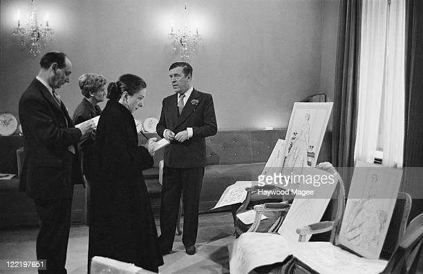 British fashion designer Norman Hartnell , receiving visitors to his Bruton Street salon in Mayfair, London, June 1953. The guests are sketching...
