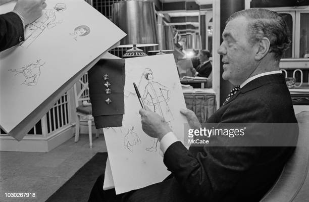 British fashion designer Norman Hartnell studying new sketches UK 29th September 1964
