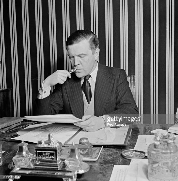 British fashion designer Norman Hartnell working at his Bruton Street salon in Mayfair, London, 31st January 1947.