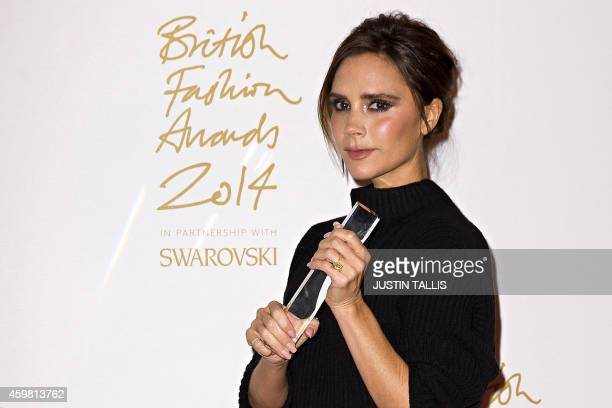British fashion designer Victoria Beckham poses for pictures with her Brand award during the British Fashion Awards 2014 in London on December 1 2014...