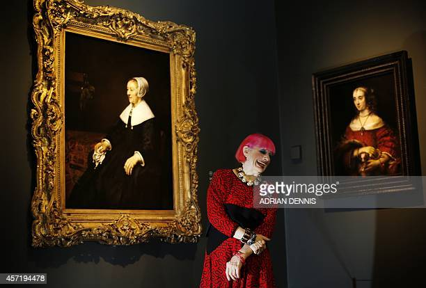 British fashion designer Zandra Rhodes is pictured in front of a painting entitled 'Portrait of Catrina Hooghsaet' by Dutch artist Rembrandt during a...