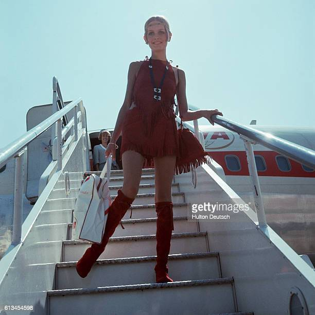 British fashion model and actress Twiggy, , disembarks from an aircraft in a 1960s-style red suede velvet outfit. | Location: London Airport, London,...
