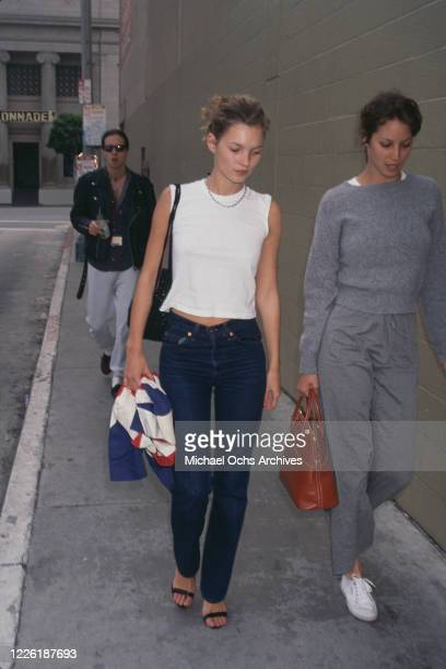 British fashion model Kate Moss, wearing a sleeveless white t-shirt and dark blue jean, walking with an unidentified woman, 1994.