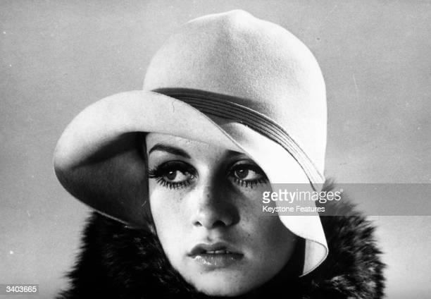British fashion model Twiggy modelling a felt cloche hat.