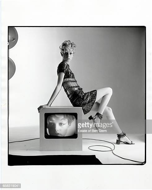 British fashion model Twiggy sitting on a television showing an image of her face in a shoot for Vogue Magazine Paris 1967