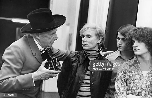 British fashion photographer Cecil Beaton talks with American pop artist Andy Warhol and twin brothers Jed and Jay Johnson as he takes photographs in...